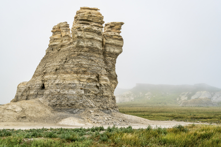 castle rock: Castle Rock - limestone pillar landmark in prairie of western Kansas near Quinter (Gove County) , foggy summer morning