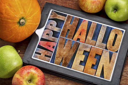 Happy Halloween greeting card -  text in vintage grunge wood type printing blocks on a digital tablet with a pumpkin and apples Stock Photo