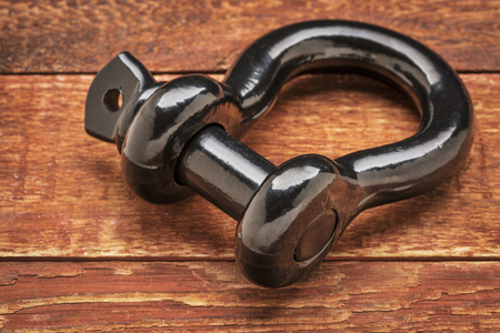 dring: heavy duty shackle (d-ring) for vehicle recovery and towing on rustic red painted wood