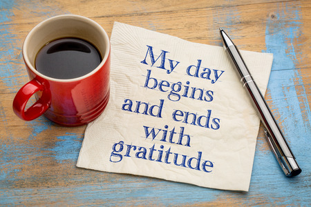 affirmation: My day begins and ends with gratitude - positive affirmation words - handwriting on a napkin with a cup of coffee Stock Photo