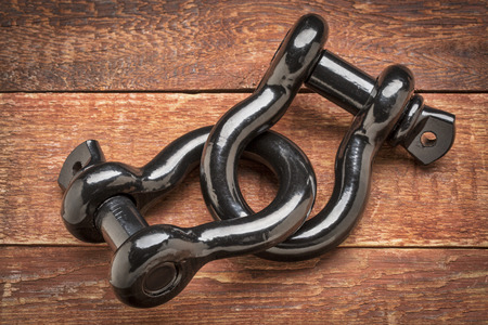 dring: two connected heavy duty shackle (d-ring) for vehicle recovery and towing on rustic red painted wood - strong link or connection concept