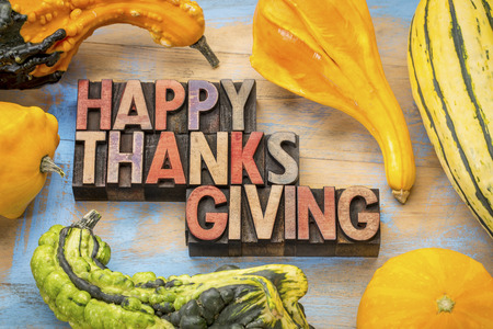 woodtype: Happy Thanksgiving - a greeting card or banner in vintage letterpress wood type blocks against wood with gourd and winter squash Stock Photo