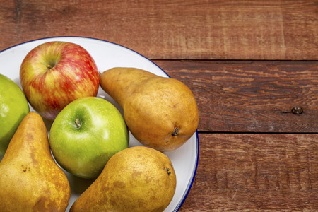 space wood: apples and pears on rustic red painted barn wood table with a copy space Stock Photo