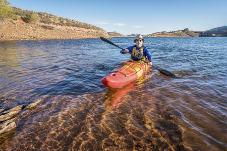 horsetooth reservoir: senior male is paddling  a mountain lake Horsetooth Reservoir) - recreation concept