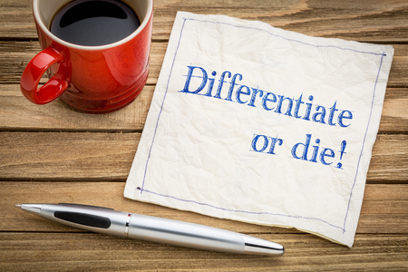 Differentiate or die!  Handwriting on a napkin with a cup of espresso coffee Banco de Imagens