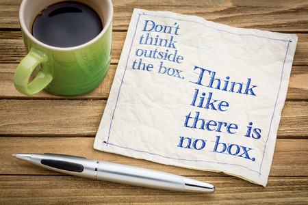 Dont think outside the box. Think like there is no box.- handwriting on a napkin with a cup of espresso coffee