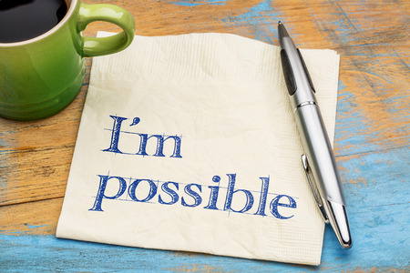 affirmation: Im possible - handwriting on a napkin with a cup of coffee