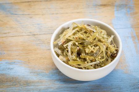 algas marinas: un pequeño cuenco de cerámica de ensalada de algas sobre la base de agar-agar contra la madera del grunge