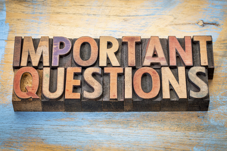 crucial: important questions - word abstract in vintage letterpress wood type against grunge painted wood Stock Photo