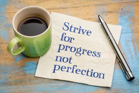 Lottare per il progresso, non la perfezione - scrittura a mano su un tovagliolo con una tazza di caffè espresso