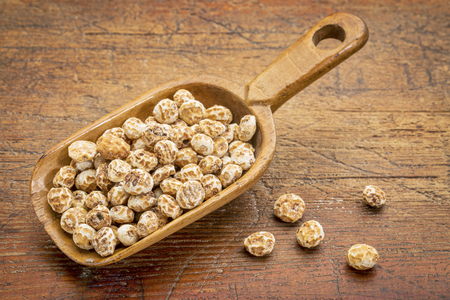 organic peeled tiger nuts, a rich source of resistant starch, wooden scoop against rustic wood Reklamní fotografie