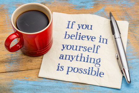 If you believe in yourself  anything is possible - handwriting on a napkin with a cup of espresso coffee