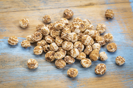 organic peeled tiger nuts, a rich source of resistant starch,a small pile against grunge wood
