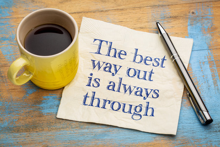 way out: The best way out is always through - handwriting on a napkin with a cup of espresso coffee