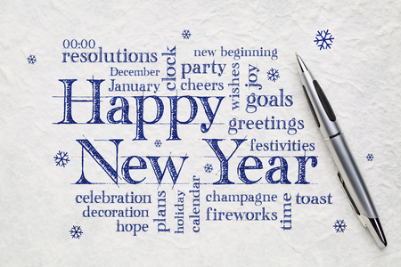 Happy New Year greeting card - word cloud on white lokta paper wit a pen Imagens