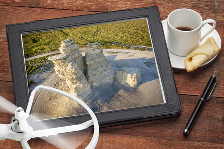 castle rock: aerial photography concept - reviewing aerial pictures of the Castle Rock landmark in Kansas on  a digital tablet with a drone rotor and coffee, screen picture copyright by the photographer