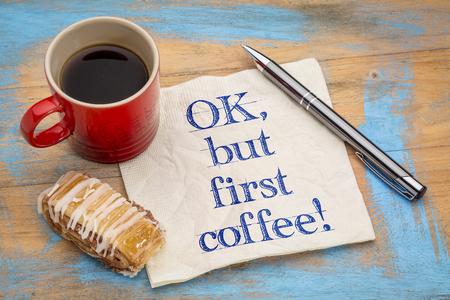 OK, maar eerst koffie - vrolijke handschrift op een servet met een pen, kopje espresso koffie en koekje tegen grunge geschilderd hout