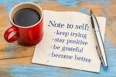 grateful: Note to self : goals and resolutions - handwriting on a napkin with a cup of espresso coffee Stock Photo
