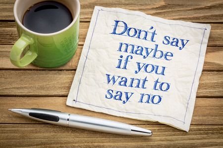 Dont say maybe if you want to say no - handwriting on a napkin with a cup of espresso coffee