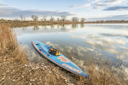 starboard: FORT COLLINS  CO, USA - November 5, 2016: All Star racing stand up paddleboard by Starboard in brushed carbon layout with Werner paddle and mesh duffel on a shore of a calm lake with late fall scenery Editorial