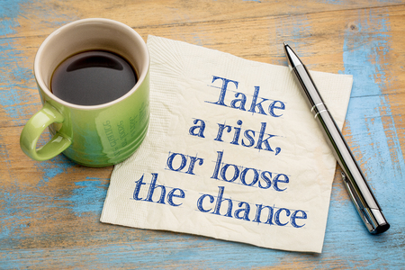 Take a risk or loose the chance - handwriting on a napkin with a cup of espresso coffee