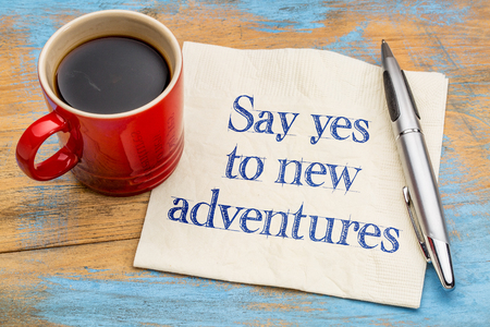 Say yes to new adventures - handwriting on a napkin with a cup of espresso coffee