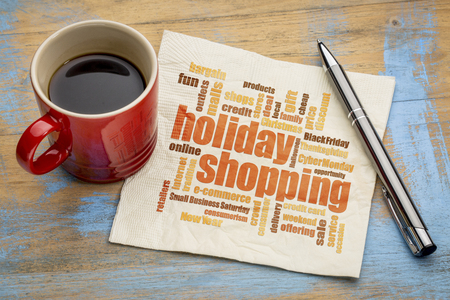 holiday shopping word cloud on a napkin with a cup of coffee