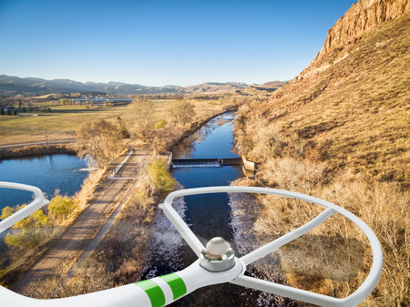 poudre river: drone flying over rural Colorado - river, diversion dam, lake and sandstone cliff