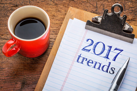 trend: 2017 trends on a  clipboard with coffee against grunge wood desk
