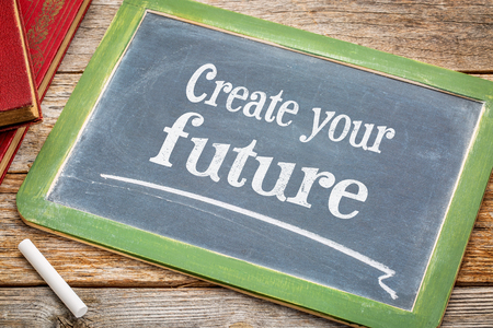 create your future - text on a slate blackboard with a white chalk and a stack of books against rustic wooden table
