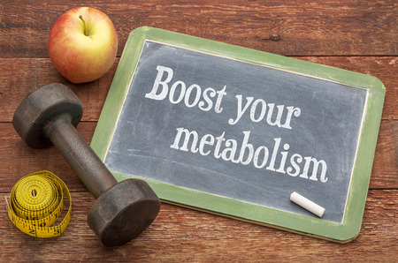 Boost your metabolism concept - slate blackboard sign against weathered red painted barn wood with a dumbbell, apple and tape measure