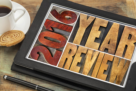 commentary: 2016 review banner - annual review or summary of the recent year - word abstract in vintage letterpress wood type blocks on a digital tablet with coffee