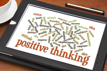 unorthodox: positive thinking and attitude word cloud on a digital tablet with a cup of tea