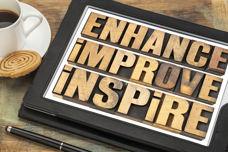 letterpress words: enhance, improve, inspire word abstract  - a collage of motivational words in vintage letterpress wood type on a digital tablet with a cup of coffee