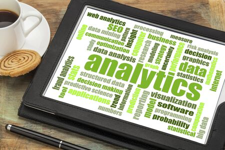 analytics and data analysis word cloud on a  digital tablet with a cup of coffee 版權商用圖片
