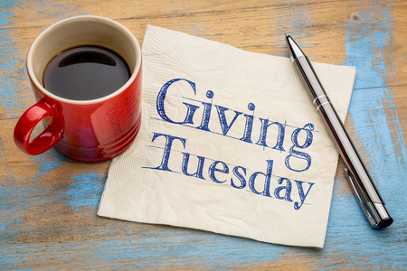 commercialization: Giving Tuesday  - handwriting on a napkin with a cup of espresso coffee