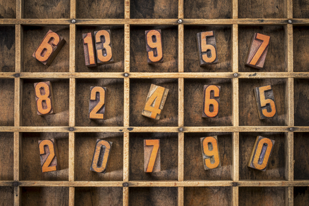 typesetter: random letterpress numbers stained by black ink in old typesetter case with dividers