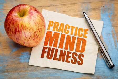 mindfulness: Practice mindfulness - motto or resolution on a napkin with an apple