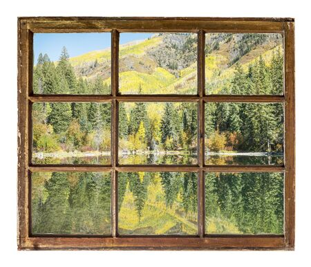 window frame: Mountain lake with fall colors as seen  through vintage, grunge, sash window with dirty glass