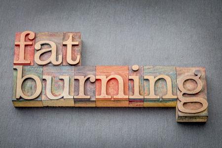 fat burning word abstract in letterpress wood type against a gray slate rock Reklamní fotografie