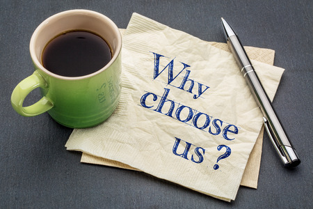 Why choose us? Handwriting on a napkin with cup of coffee against gray slate stone background