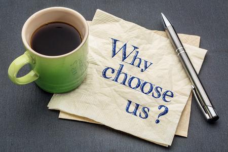 Warum Uns Wählen? Handschrift auf eine Serviette mit einer Tasse Kaffee vor grauem Schiefer Stein Hintergrund