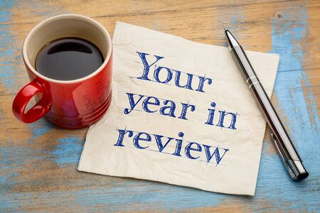review: Your year in review  - handwriting on a napkin with a cup of espresso coffee