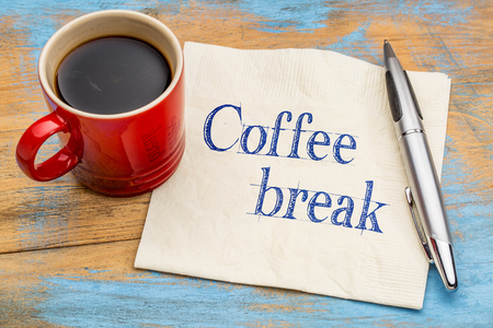 Coffee break handwriting on a napkin with a stoneware cup