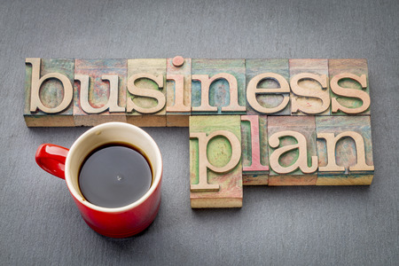 business plan word abstract  -  text in letterpress wood type printing blocks with a cup of coffee