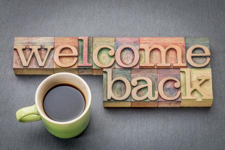 Witamy z powrotem znak - tekst w rodzaju drewna typografii z filiżanką kawy
