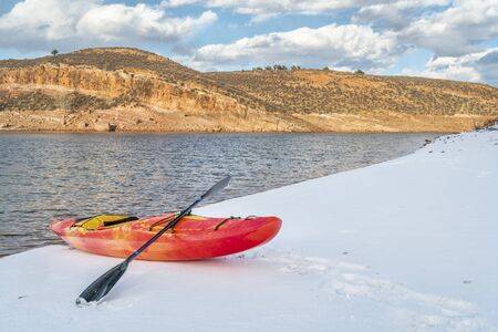 horsetooth reservoir: winter kayaking in Colorado - red whitewater kayak on shore of Horsetooth Reservoir near Fort Collins