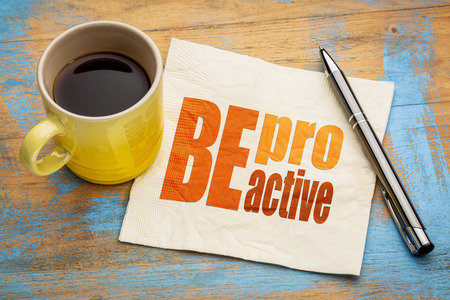 be proactive word abstract on a napkin with a cup of coffee Foto de archivo