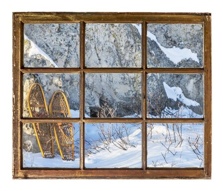 window frame: winter scene with vintage classic snowshoes as seen from a sash window of old cabin Stock Photo