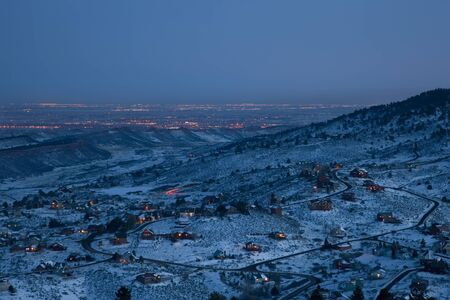 loveland: night time winter view from mountains towards plains near Fort Collins and Loveland in Colorado with mountain houses and distant city lights over plains